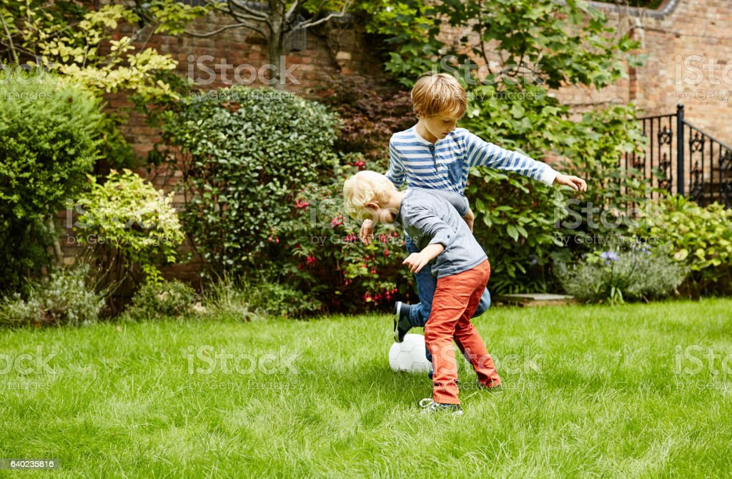 Showing his big brother some soccer skills stock photo