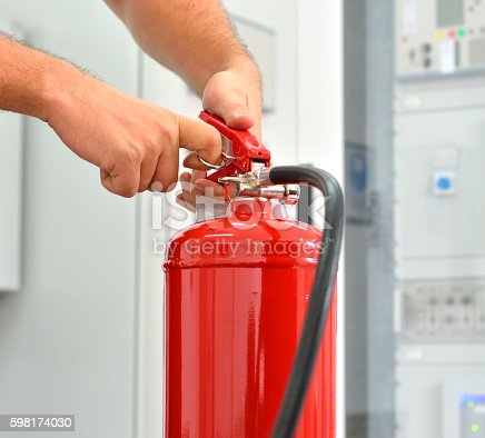 Worker demonstrates the use of fire extinguishers. Pulling the safety pin on a fire extinguisher.