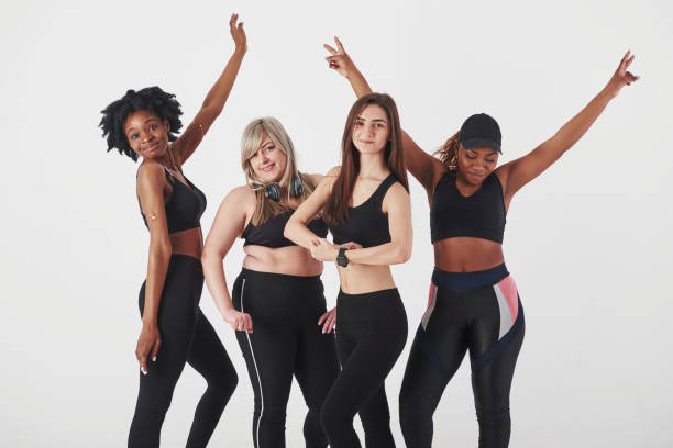 Showing off the bodies. Group of multi ethnic women standing in the studio against white background stock photo