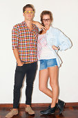 A young hipster couple standing against a white wall while wearing glasses