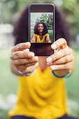 Portrait of beautiful mixed-race woman taking selfie