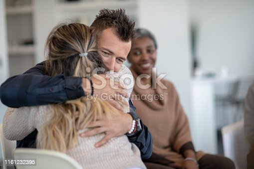A young caucasian man is hugging a female during a group therapy session. He is hugging her tight and feeling a sense of relief.
