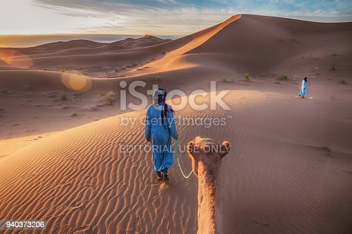 Two Muslim men dressed in blue robes wearing headscarves walking through the sand dunes of the Sahara Desert, leading a camel at sunrise, with golden light and lens flare.