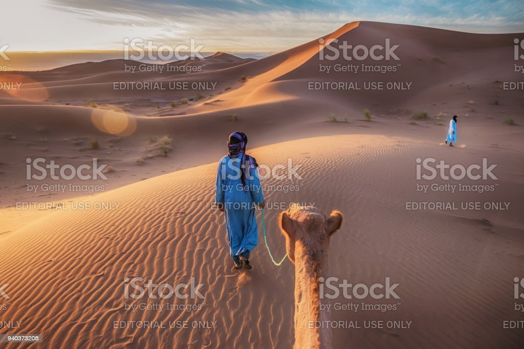 Showing the traditional blue clothing and mode of transportation of nomadic Tuareg tribesmen in the Sahara Desert, as they walk through the sand dunes with camels. – zdjęcie