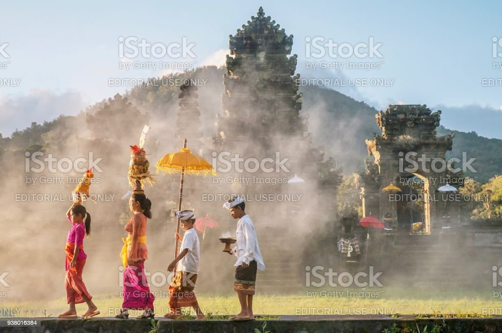 Showing traditional Balinese male and female ceremonial clothing and religious offerings as a mother and children walk to a Hindu temple (pura) in Bali. stock photo
