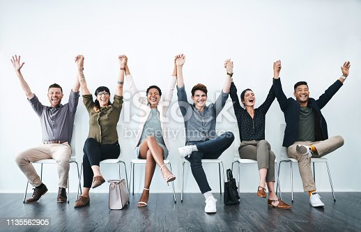 Studio shot of a group of businesspeople holding hands and cheering in a waiting room