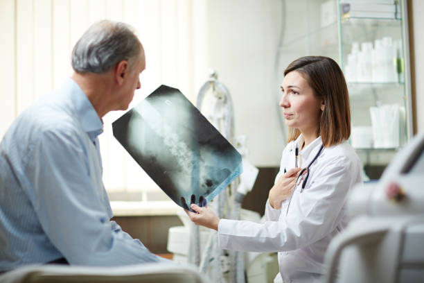 showing x-ray to patient - medical x ray stock pictures, royalty-free photos & images