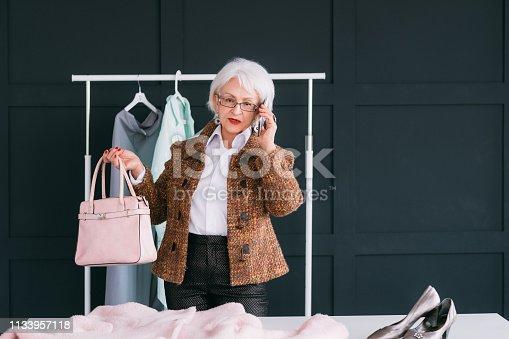1133515238 istock photo showroom vip senior business woman shopping trendy 1133957118