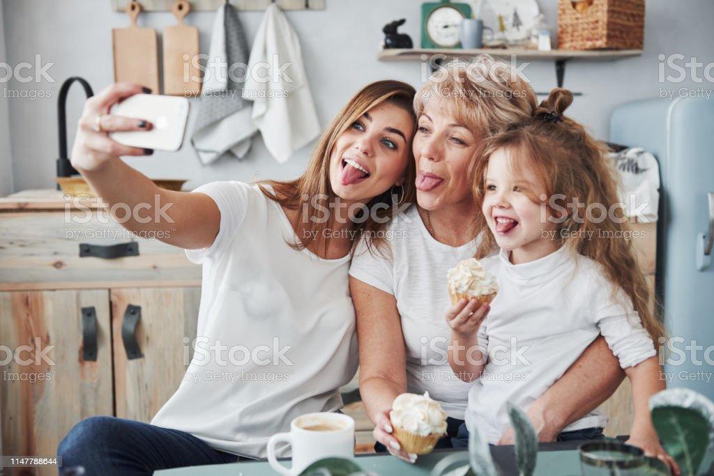 Toont tongen. Moeder, oma en dochter hebben goede tijd in de keuken - Royalty-free Alleen volwassenen Stockfoto