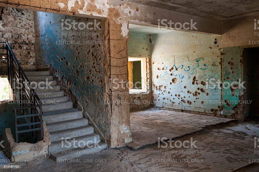 Shrapnel and bullet-scarred building in Quneitra, Syria stock photo