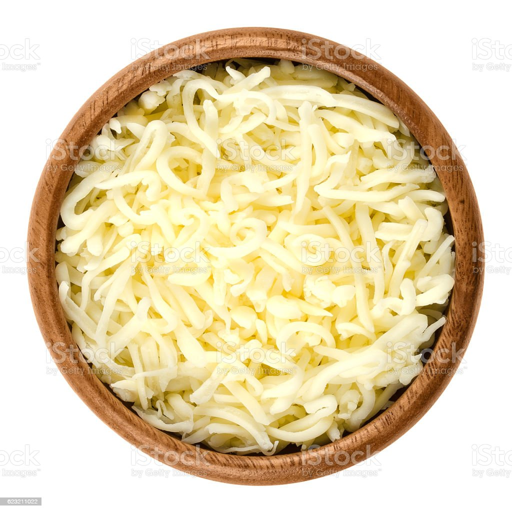 Shredded mozzarella pizza cheese in wooden bowl over white stock photo