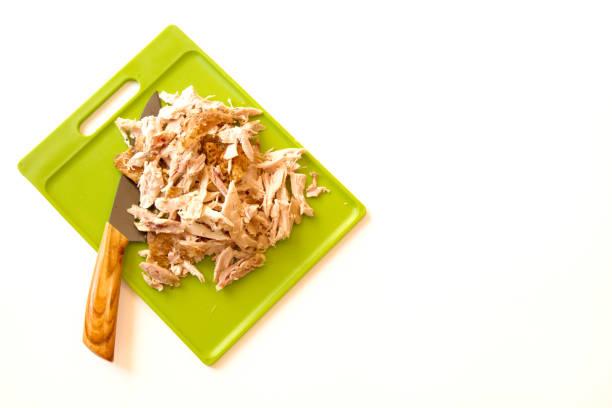 shredded rotisserie chicken isolated on white background - girarrosto foto e immagini stock