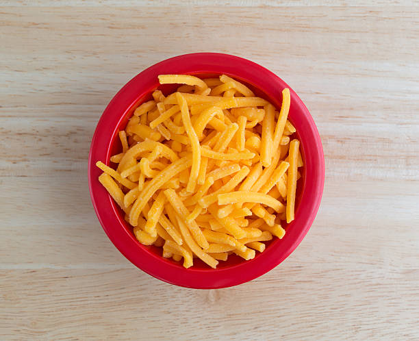 Shredded sharp cheddar cheese in red bowl Top view of a bowl of shredded sharp cheddar cheese on a wood table top illuminated with natural light. cheddar cheese stock pictures, royalty-free photos & images