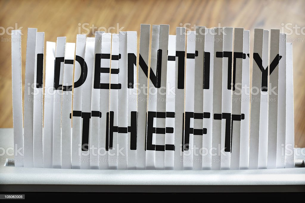 Shredder tearing up a document that says identity theft stock photo