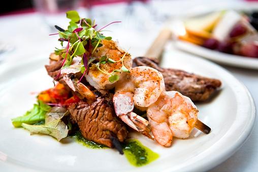 A elegantly presented plate of shrimp and beef skewers
