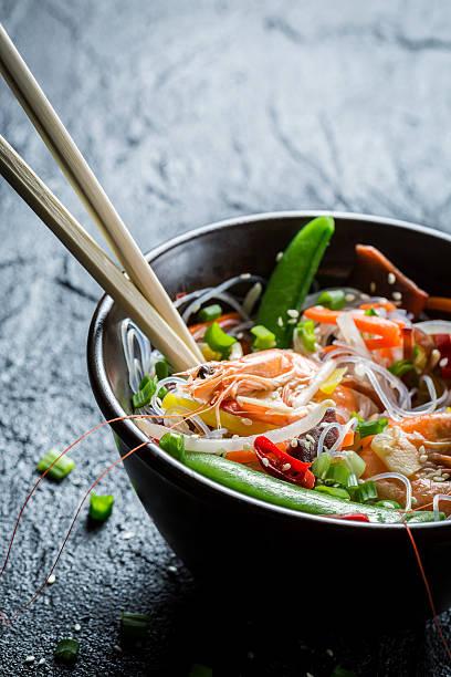 crevettes et légumes, servi avec des nouilles - cuisine asiatique photos et images de collection