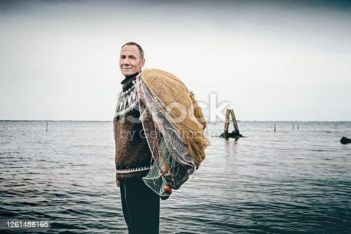 Candid portrait of a shrimp fisherman preparing his nets in the shallow water. Colour, horizontal with some copy space. The net is left in the water for 24 hours before it is hauled in and the catch sorted. Photographed on the island of Nyord in Denmark. He is fishing for salt water shrimp in the local fjord's and they are highly sought after as a delicacy here in Denmark.