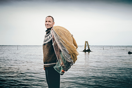 Shrimp fisherman setting out his nets in the sea.