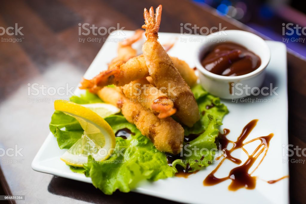 Shrimp fried in breaded folded on lettuce leaves on a white plate. royalty-free stock photo