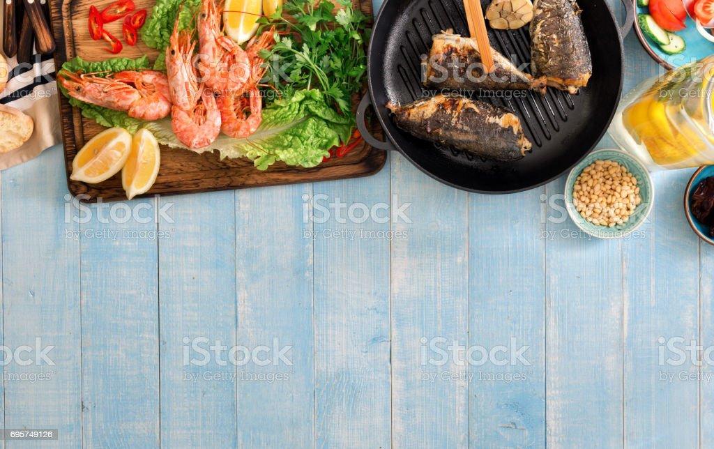 Camarones a la plancha, pescado a la parrilla en una mesa de madera azul con espacio de copia - foto de stock