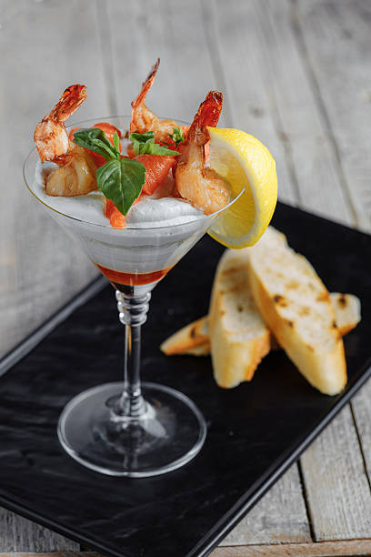 shrimp in a sauce with lemon on a wooden table stock photo