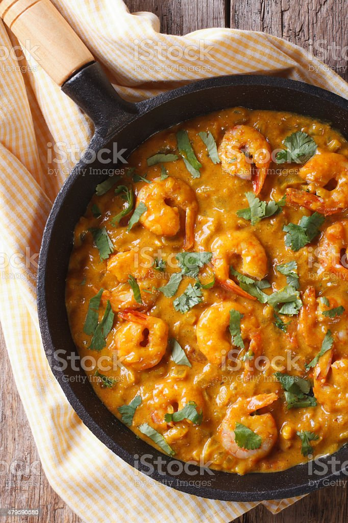 Shrimp in curry sauce in pan close-up Vertical top view stock photo