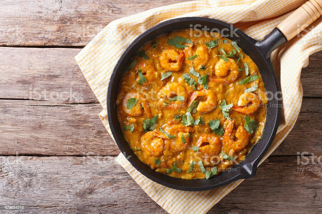 Shrimp in curry sauce in the pan. horizontal top view stock photo
