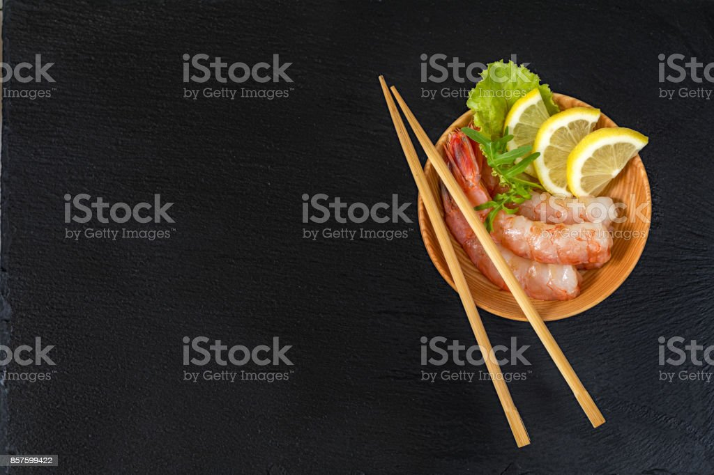 Shrimp on a wooden plate with wooden chopsticks royalty-free stock photo