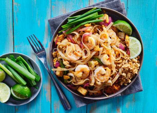 shrimp pad thai on plate in flat lay composition with copy space shrimp pad thai on plate in flat lay composition with copy space atop of colorful wooden table rice noodles stock pictures, royalty-free photos & images