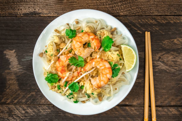 Shrimp Pad Thai plate from above with copy space An overhead photo of a Shrimp Pad Thai, traditional Thai dish with stir fried rice noodles, shot from above on a rustic texture with chopsticks and copy space rice noodles stock pictures, royalty-free photos & images