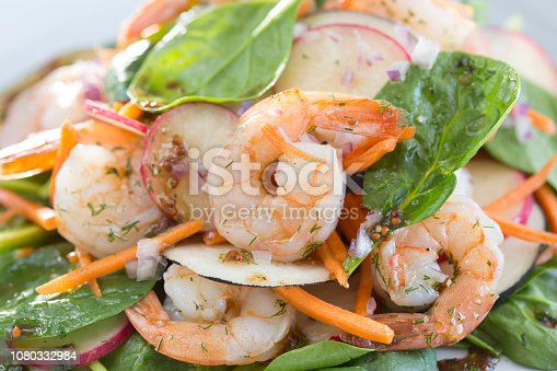 Shrimp salad with spinach leaves, radish slices and some carrot grated with olive oil, mustard seeds and balsamic vinegar. Selective focus. High key. Studio photography. Horizontal composition.