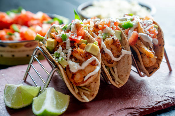 Shrimp Street Tacos Shrimp Street Tacos with all the Trimmings like Avocado, Sour Cream and Cotilla Cheese on a Rustic Slate to be Served in a Trendy Restaurant taco stock pictures, royalty-free photos & images