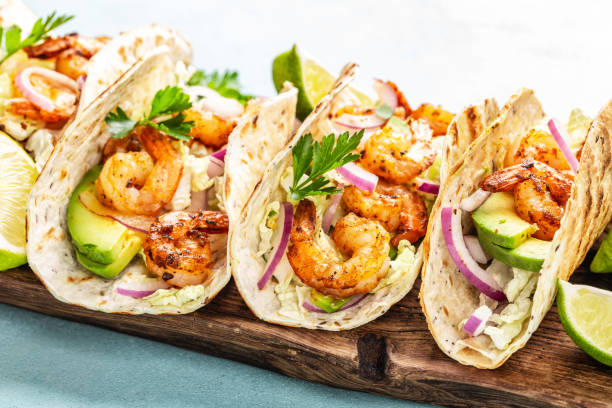 Shrimp tacos. Seafood fajitas with cabbage, onion, parsley in tortillas served on wooden cutting board Shrimp tacos. Seafood fajitas with cabbage, onion, parsley in tortillas served on wooden cutting board brassica rapa stock pictures, royalty-free photos & images