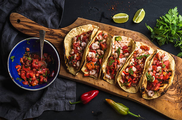 shrimp tacos with homemade salsa, limes and parsley - mexican food stock photos and pictures