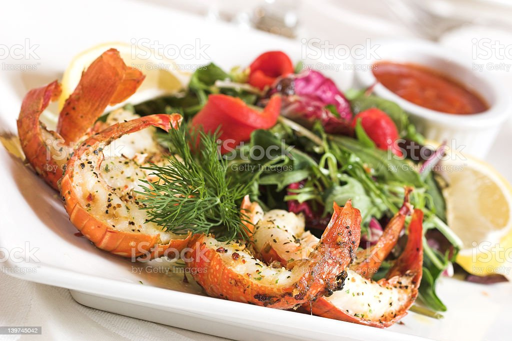 Shrimp with a side of salad and lemon with cocktail sauce stock photo