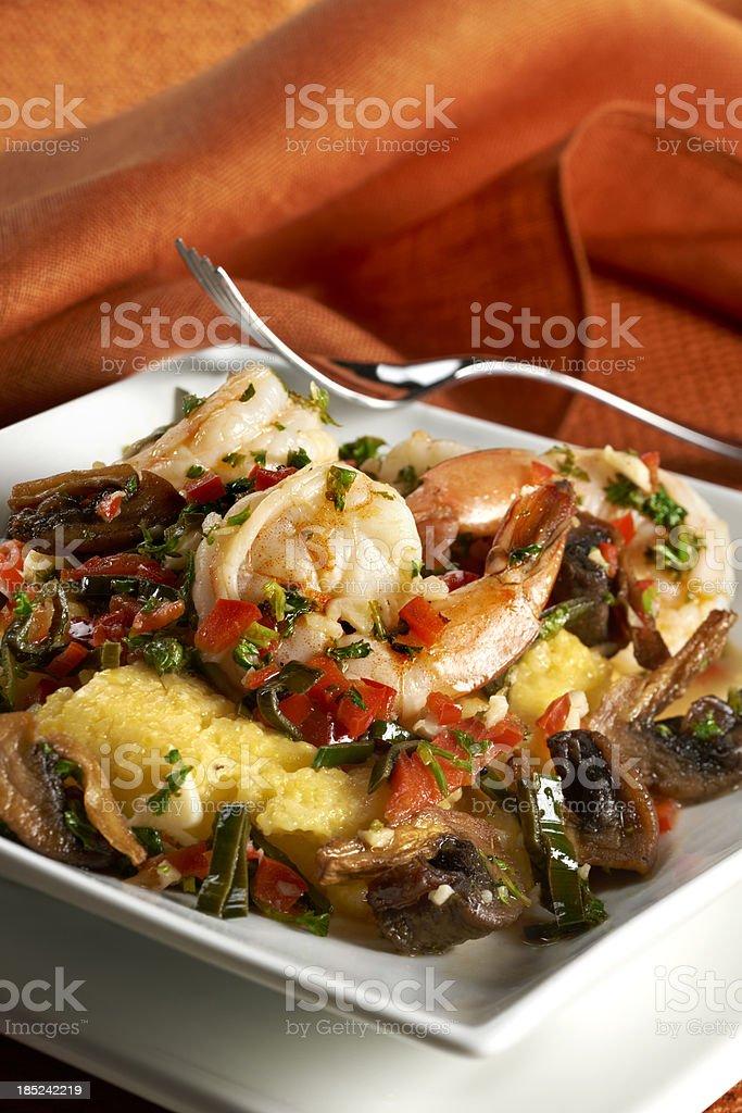 Shrimp with creamy polenta and mushrooms stock photo