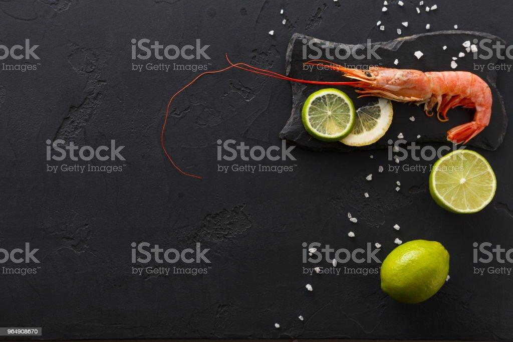 Shrimp with salt and lemon on black background royalty-free stock photo
