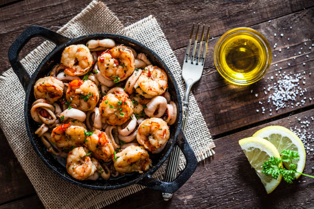 Shrimps and calamari rings cooked on iron cast pan stock photo
