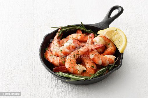 Tiger shrimps in a skillet cooking pan with cocktail sauce and seasoning
