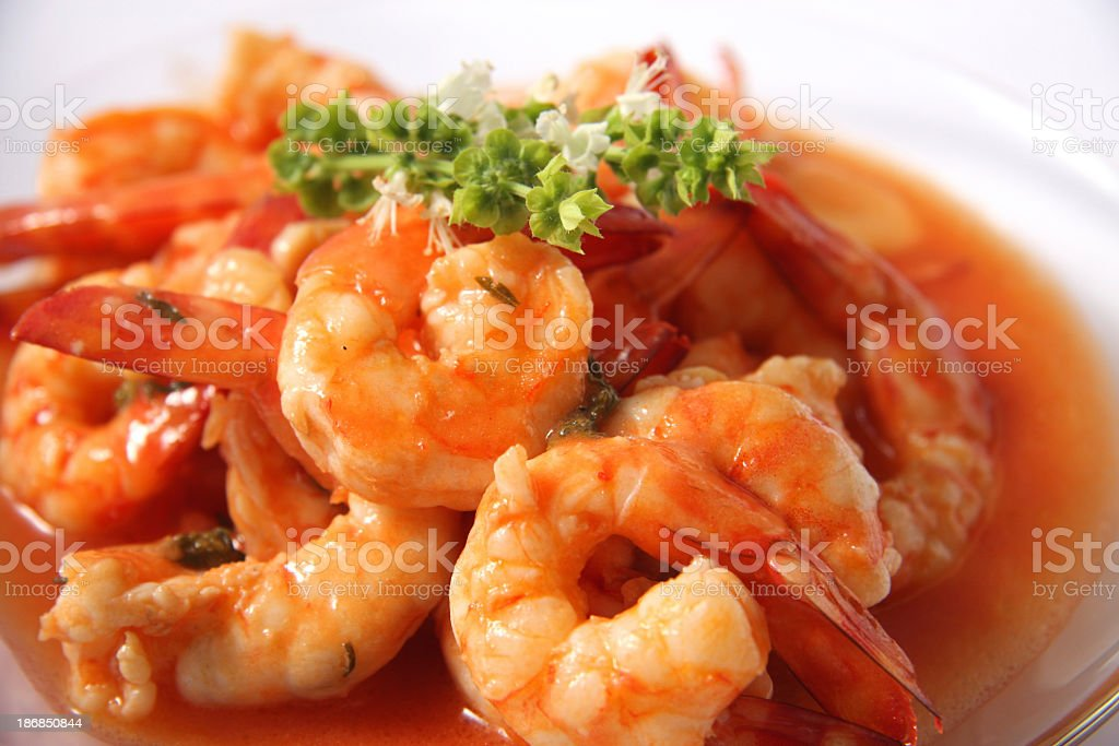 Shrimps in tomato and garlic sauce with basil leaves royalty-free stock photo