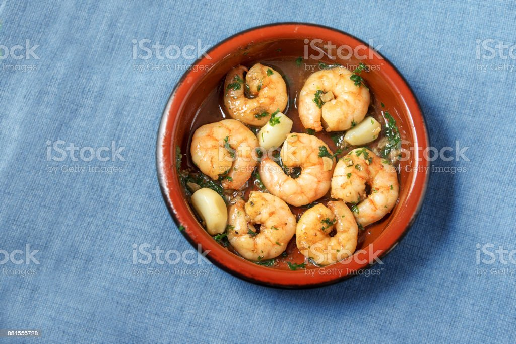 shrimps or prawns and garlic in olive oil with parsley in a brown tapas bowl, spanish appetizer on a blue tablecloth background, flat top view from above, copy space stock photo