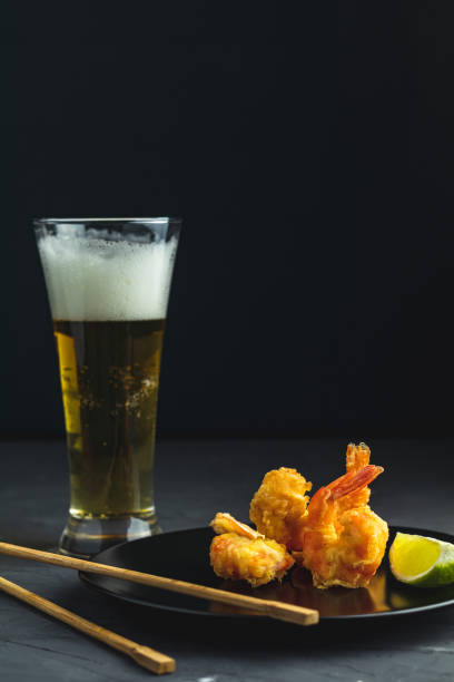 Shrimps tempura with lime in black plate and glass of light beer stock photo
