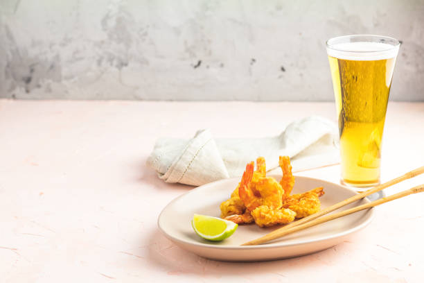 Shrimps tempura with lime in light plate and glass of beer stock photo