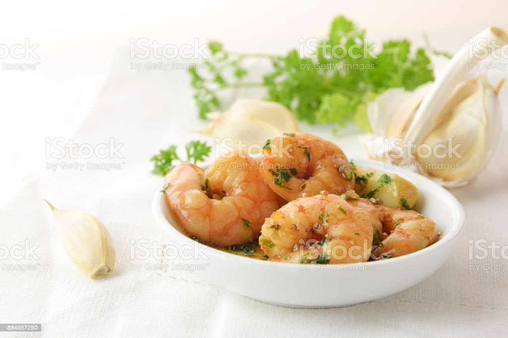 shrimps with garlic, olive oil and parsley in sherry sauce in a white bowl, spanish tapas appetizer gambas al ajillo, white napkin and herb garnish in the background, copy space stock photo