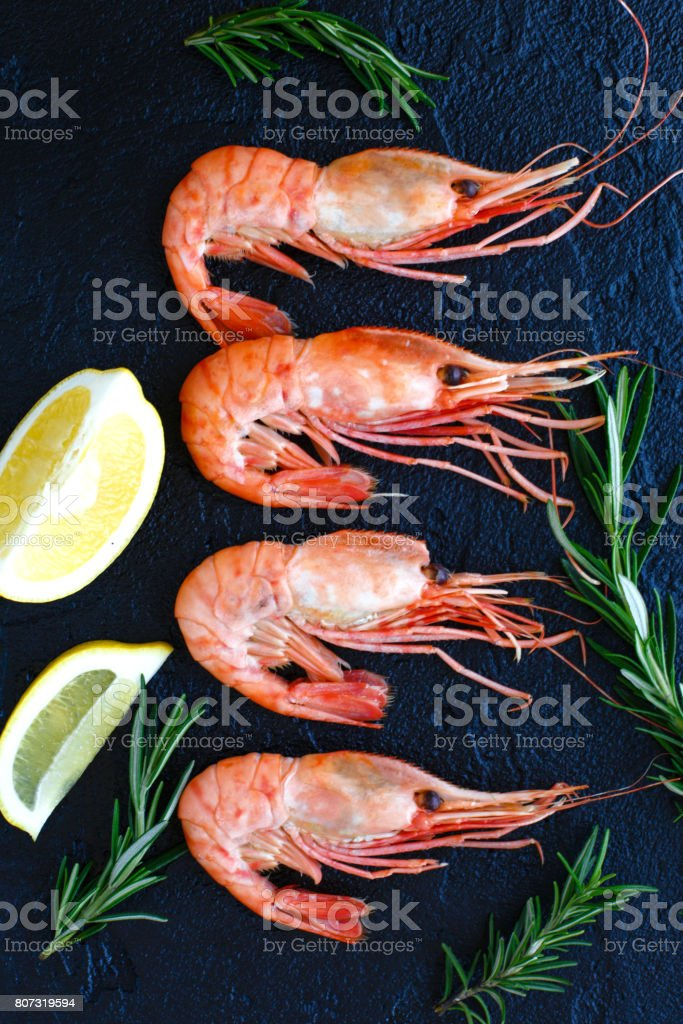 Shrimps with lemon and rosemary on a dark background stock photo