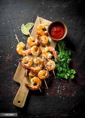 Shrimps with parsley, lime slices and tomato sauce. On dark rustic background