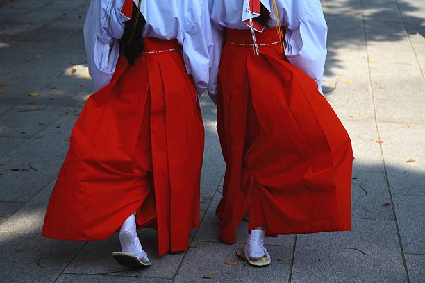 Shrine maiden walking Two Shrine maidens walking at Shinto Shrine. shinto shrine stock pictures, royalty-free photos & images