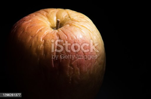 Shriveled yellow and red apple with deep wrinkles on black background.  Concept of aging.