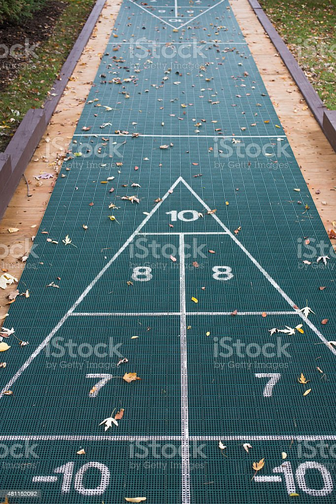 Shuffleboard on green ground with Autumn leaf stock photo