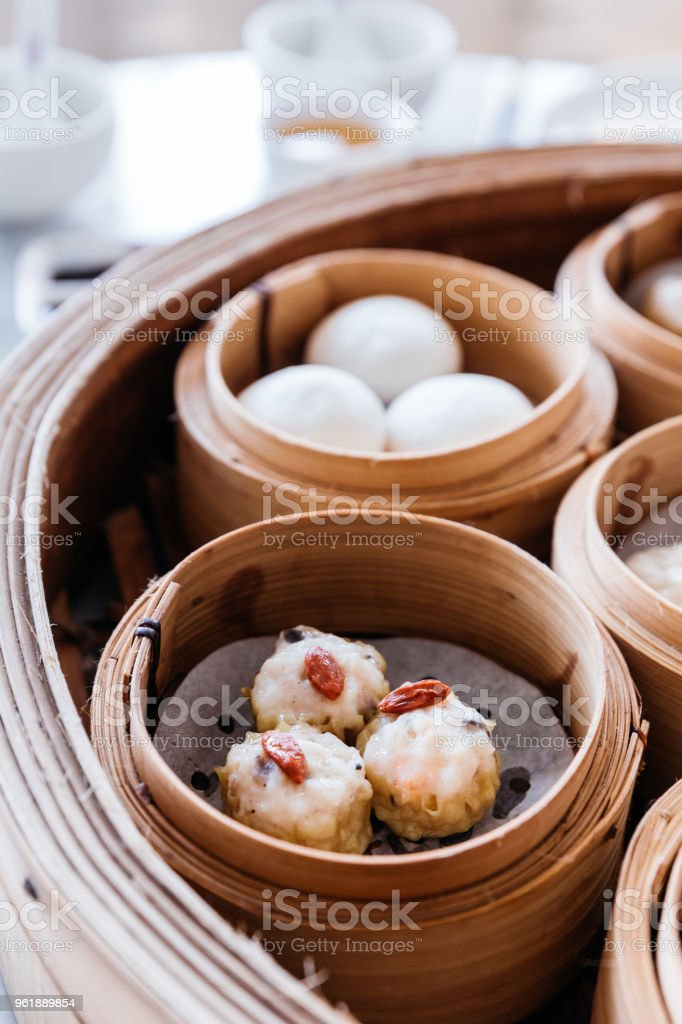 Shumai topping with goji berry served in steamer baskets with many kind of Dim sum. stock photo